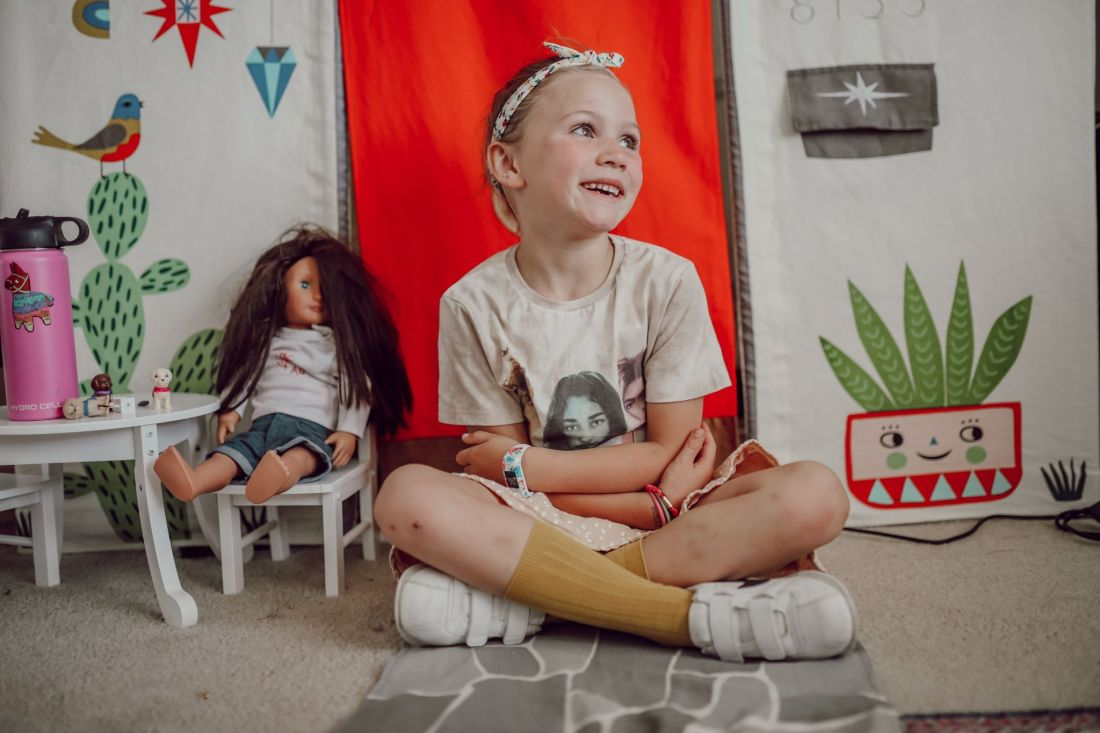 Homeschooling Journey by popular Nashville lifestyle blog, Modern Day Moguls: image of a little girl sitting in front of a fabric pop-up camper with their American Girl doll.