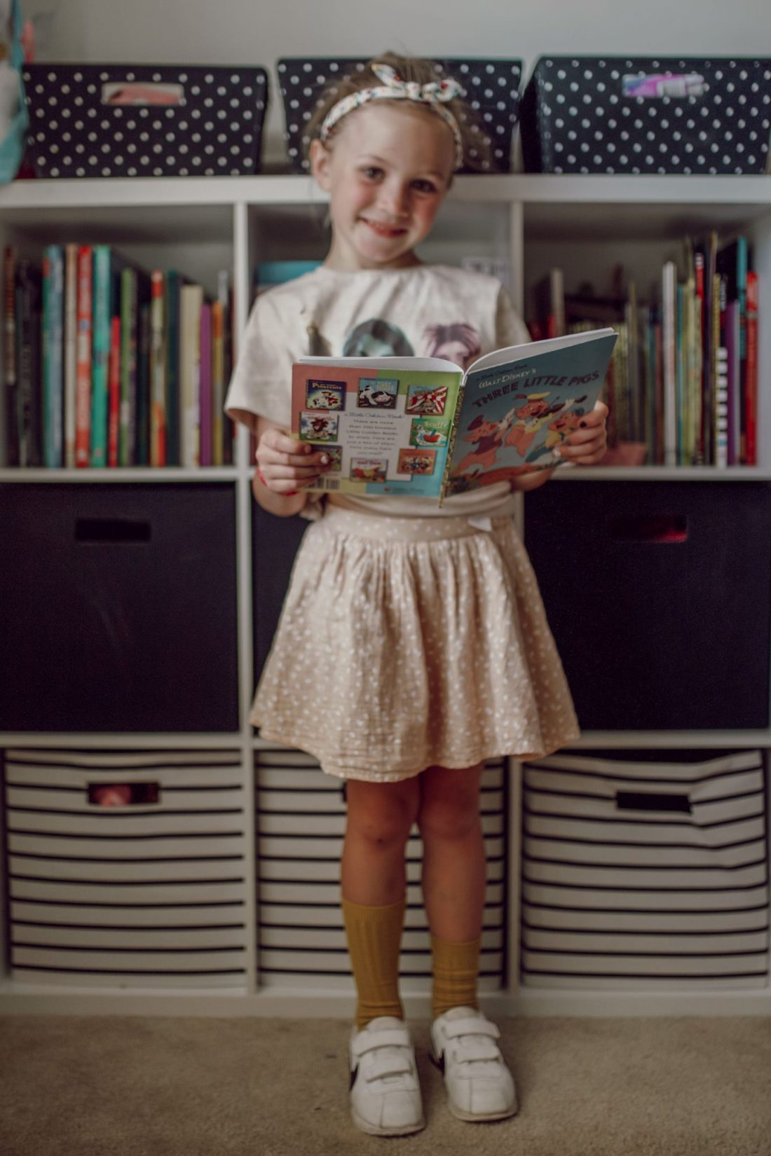 Homeschooling Journey by popular Nashville lifestyle blog, Modern Day Moguls: image of a young girl standing  next to her french bulldog and reading a book.
