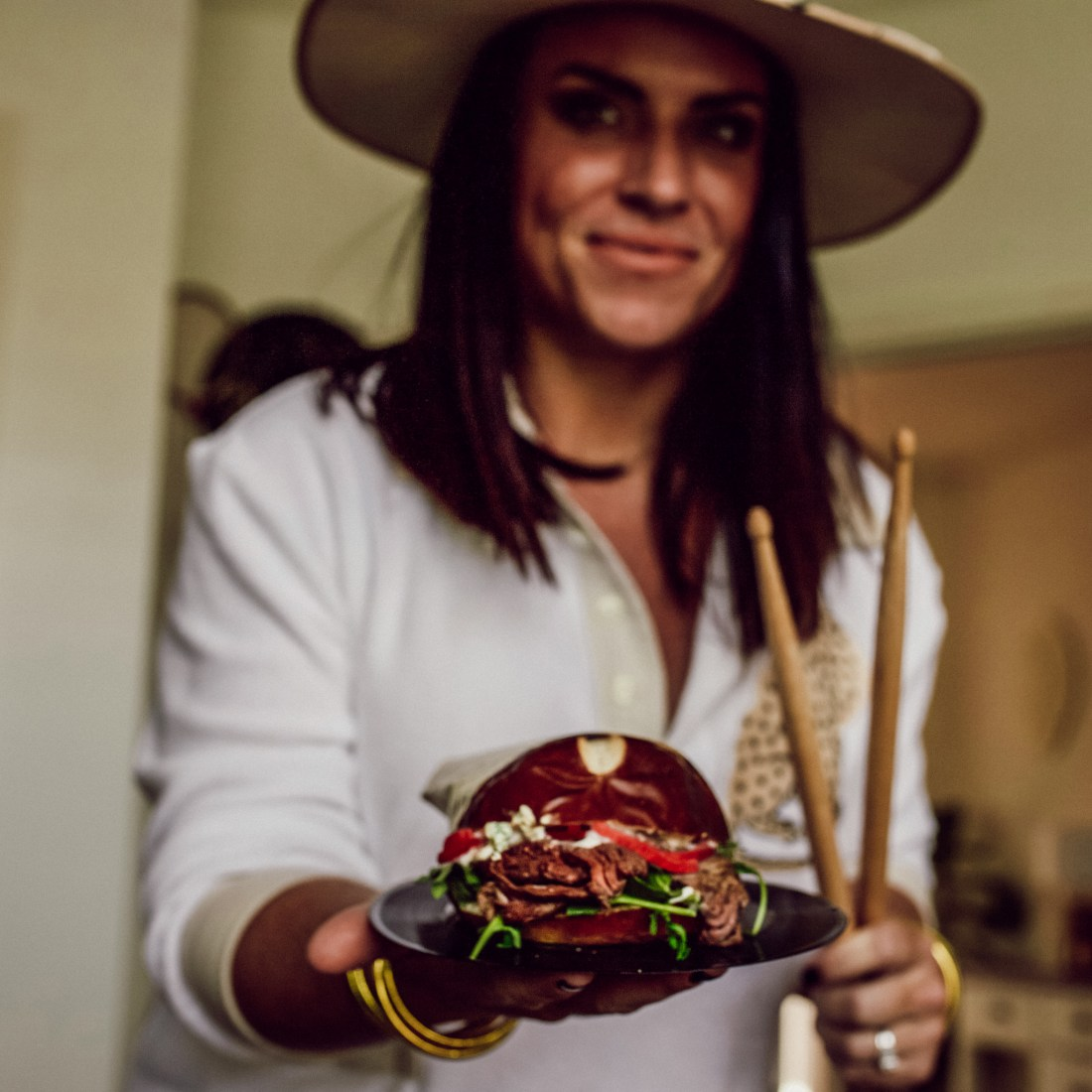 Burger and Beats by popular Nashville lifestyle blog, Modern Day Moguls: image of a woman holding a black and bleubird burger on a vinyl record.