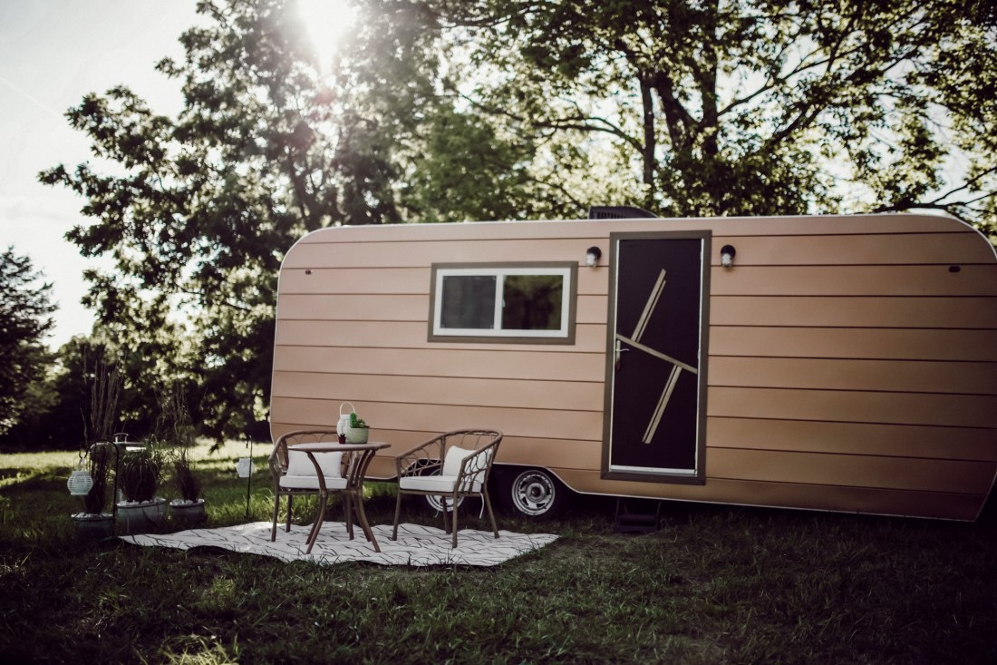 Travel Tips by popular Nashville lifestyle blog, Modern Day Moguls: image of a brown camper and a rattan table and chair set.