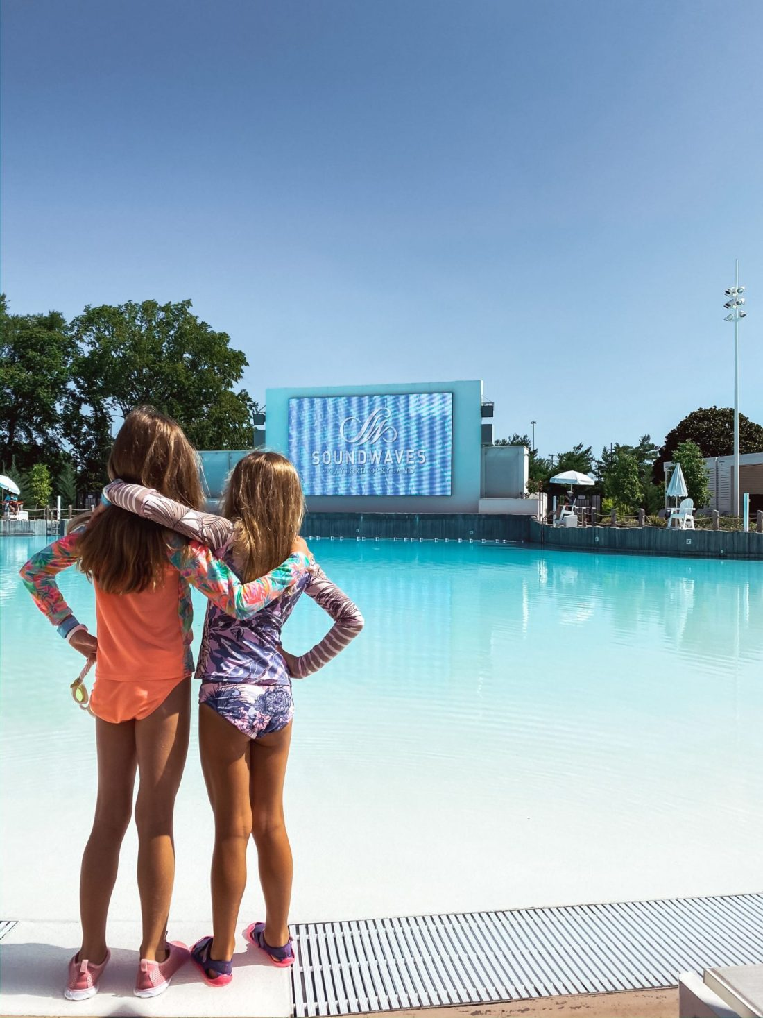 Soundwaves Water Park by popular Nashville blog, Modern Day Moguls: image of two young girls standing with their arms around each other as they stand in front of a wave pool.