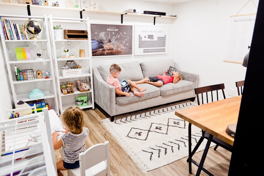 Homeshcool Room by popular Nashville life and style blog, Modern Day Moguls: image of a homeschool room with white book shelves, grey couch, computer desk and black and white rug.