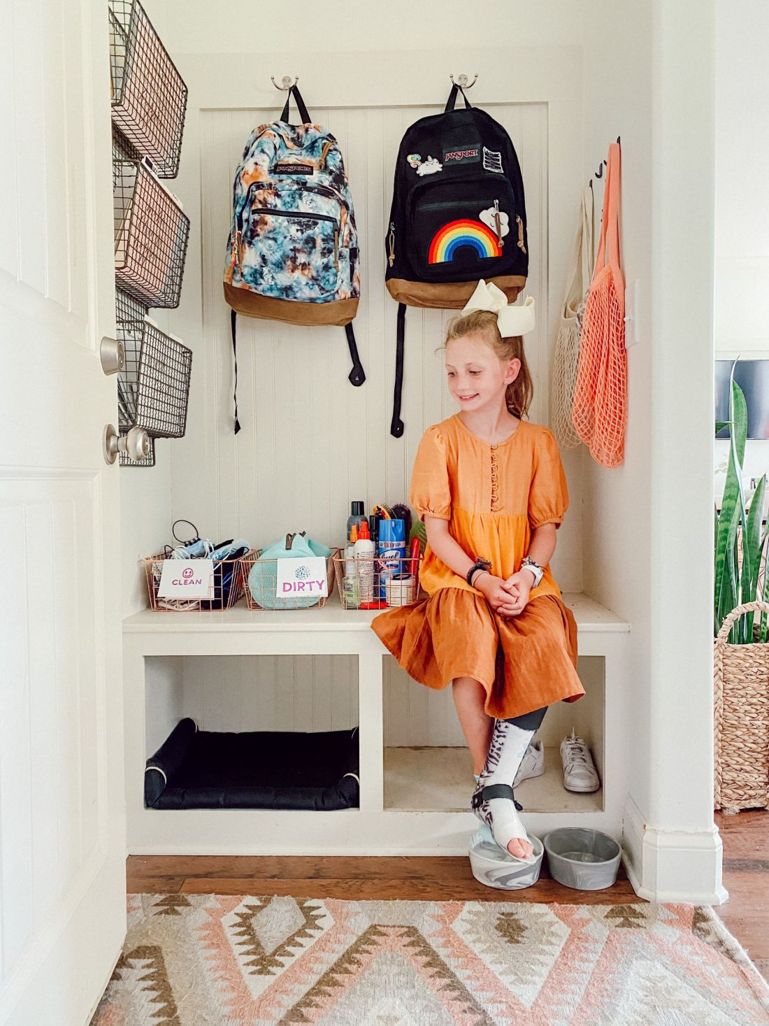 Back to School Shopping Guide by popular Nashville motherhood blog, Modern Day Moguls: image of a girl wearing a orange dress and large cream bow and sitting on a white bench and next to wire baskets filled with various supplies and two Jansport backpacks hanging on wall mounted hooks.
