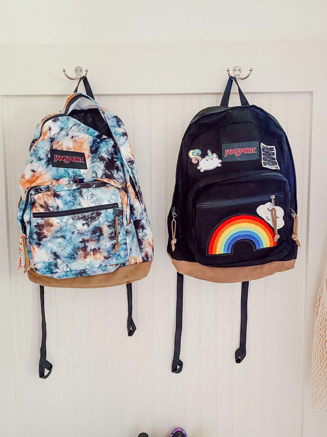 Back to School Shopping Guide by popular Nashville motherhood blog, Modern Day Moguls: image two Jansport backpacks hanging on wall mounted hooks.