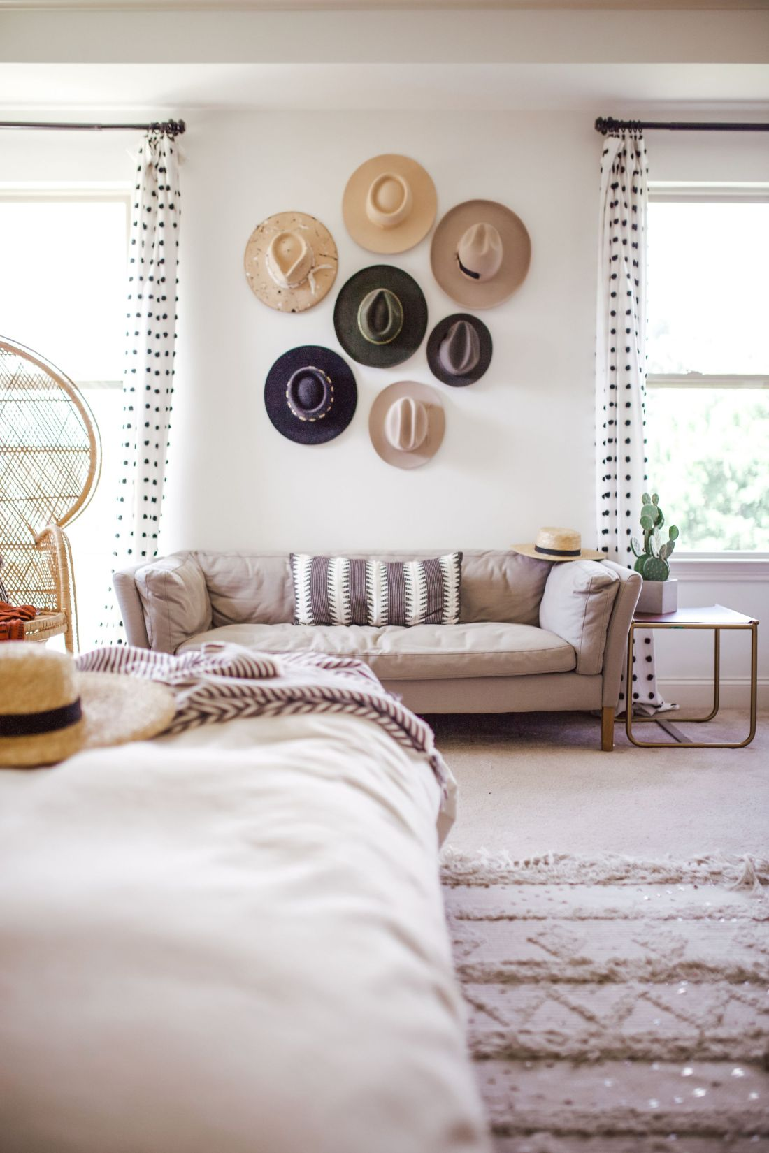 master bedroom refresh | Master Bedroom Remodel Ideas by popular Nashville life and style blog, Modern Day Moguls: image of a hat display on a wall above a beige couch that's next to a peacock chair and a end table with a cactus on it.