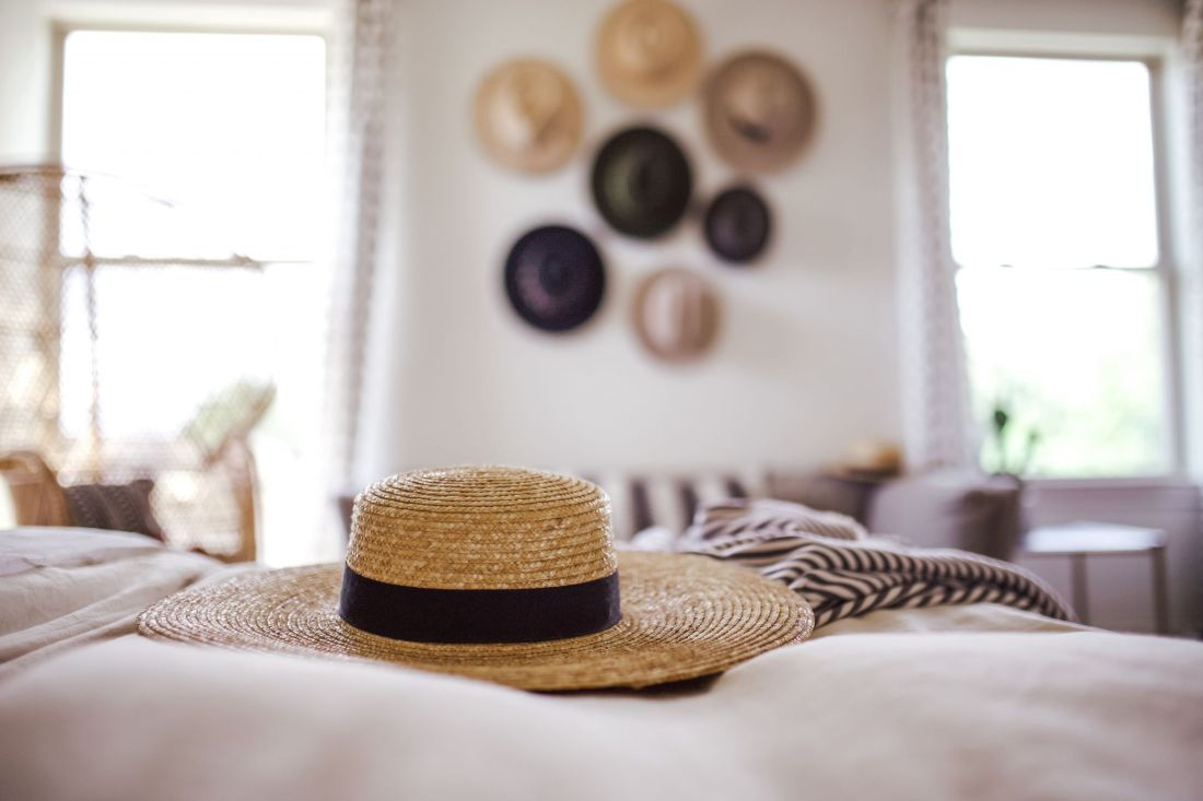 master bedroom refresh | Master Bedroom Remodel Ideas by popular Nashville life and style blog, Modern Day Moguls: image of straw boater hat on a bed next to a grey and white throw blanket with a hat display on a wall in the background.