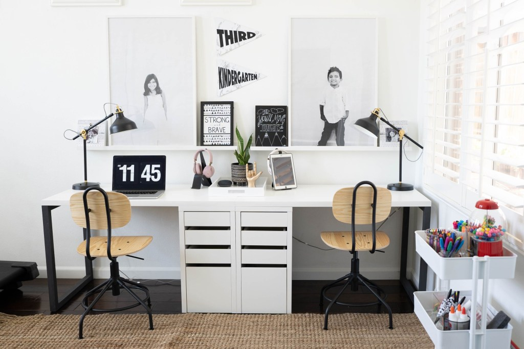 Homeshcool Room by popular Nashville life and style blog, Modern Day Moguls: image of a homeschool room with a white organization cart, white desk, black lamps, black and white photographs of kids, and wood and black metal chairs.