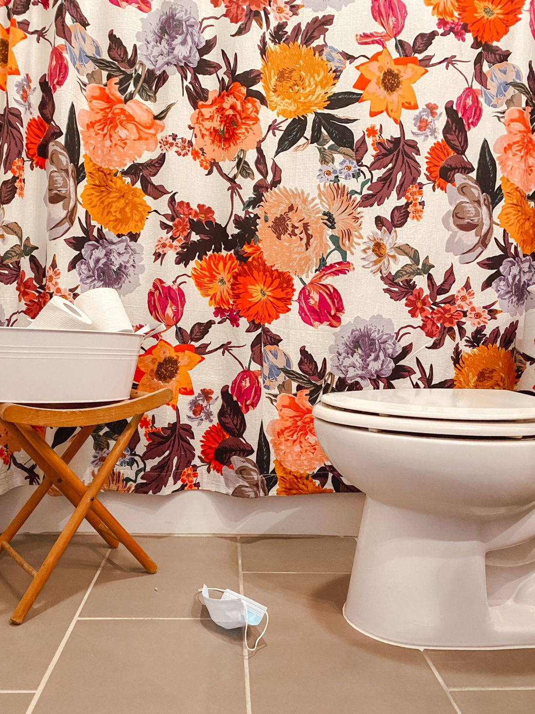 Hoffmann Brothers by popular Nashville lifestyle blog, Modern Day Moguls: image of a bathroom with a floral shower curtain, and white metal tin filled with toilet paper.