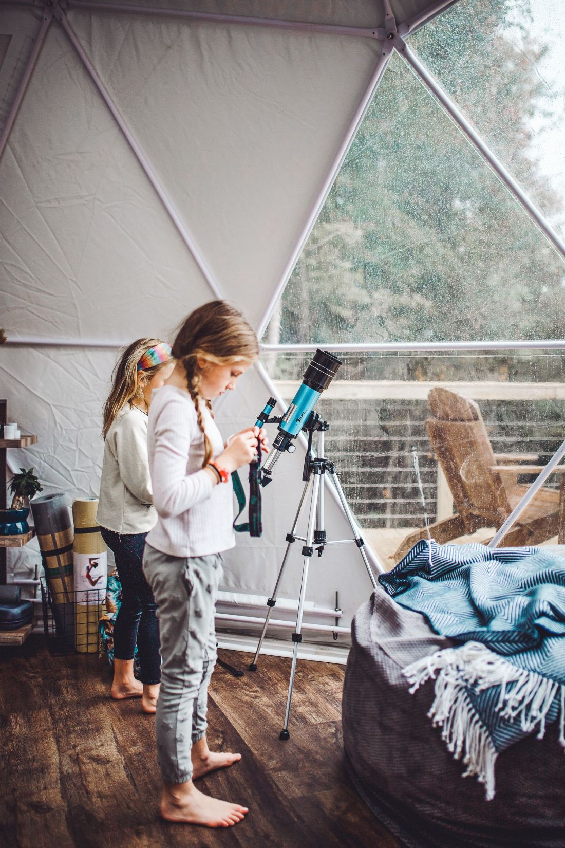 Glamping in Tennessee by popular Nashville lifestyle blog, Modern Day Moguls: image of two girls looking through a telescope in a geodesic dome.
