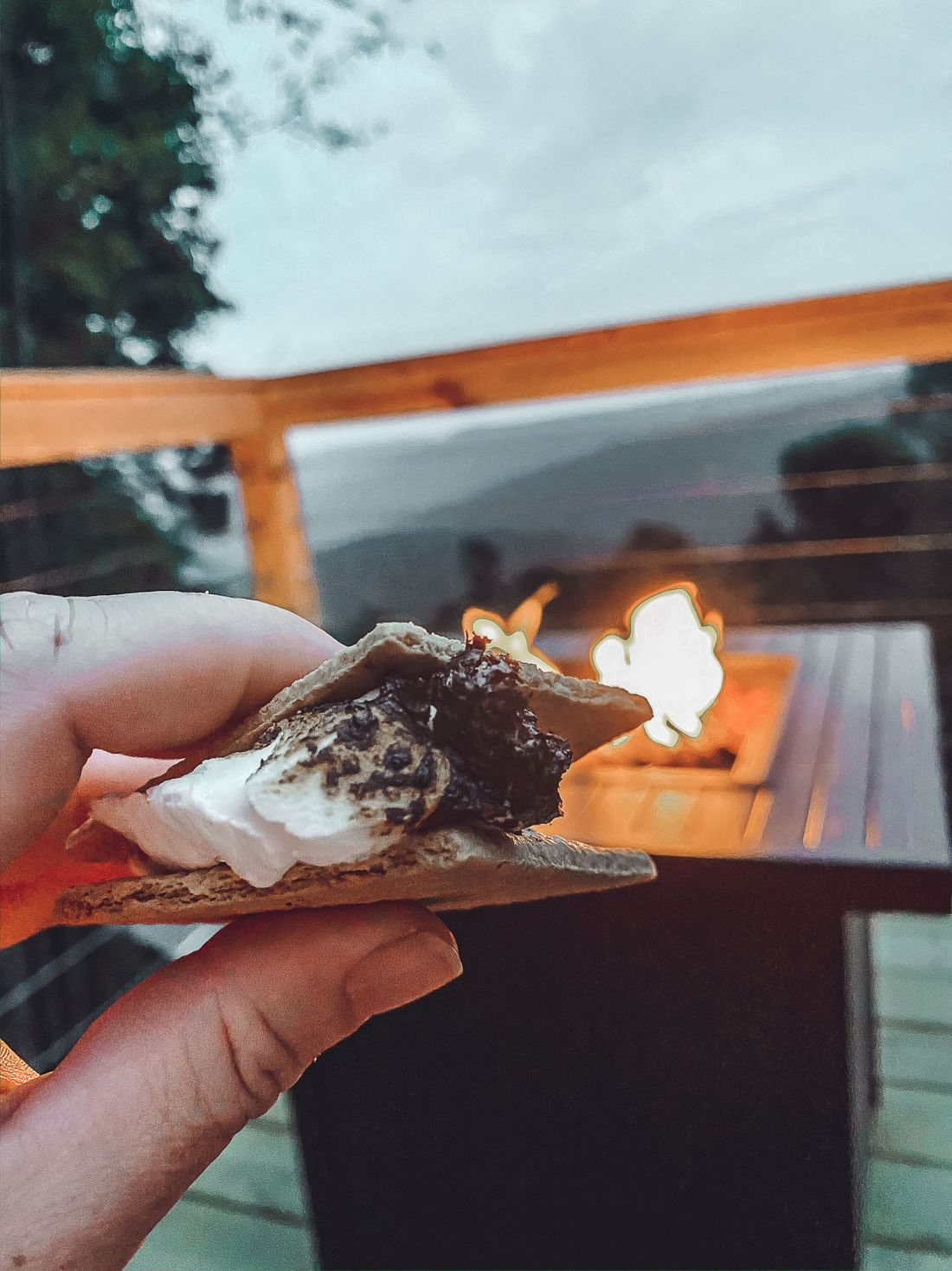 Glamping in Tennessee by popular Nashville lifestyle blog, Modern Day Moguls: image of a woman holding a s'more in her hand.