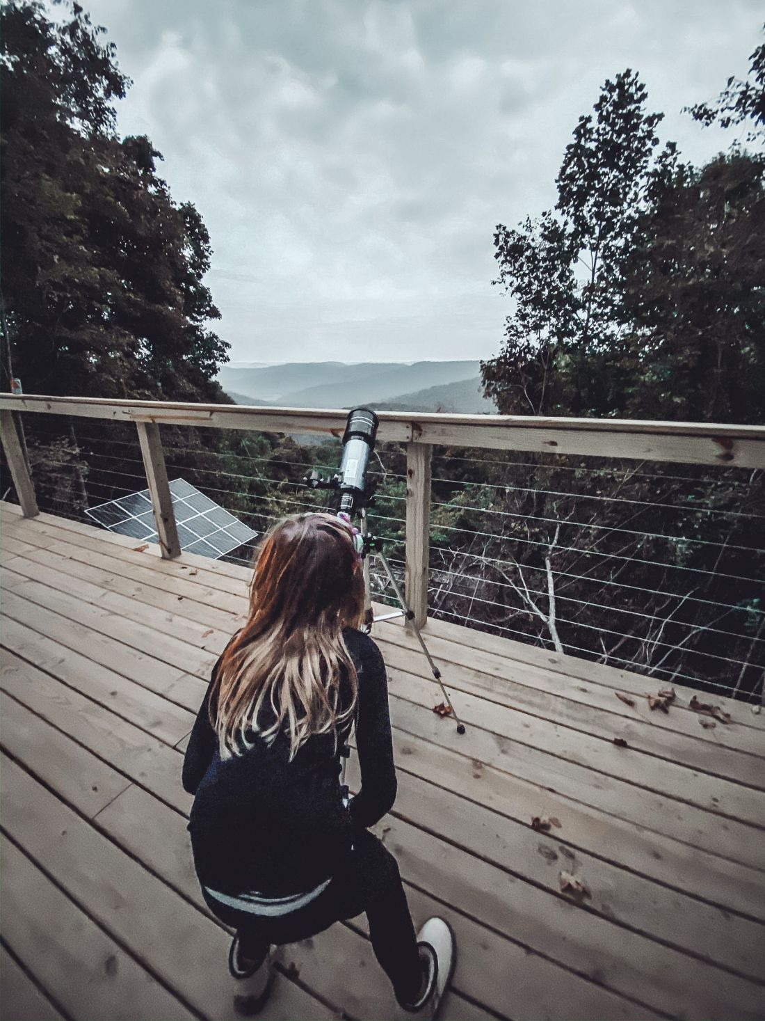 Glamping in Tennessee by popular Nashville lifestyle blog, Modern Day Moguls: image of a girl looking through a telescope on a deck.