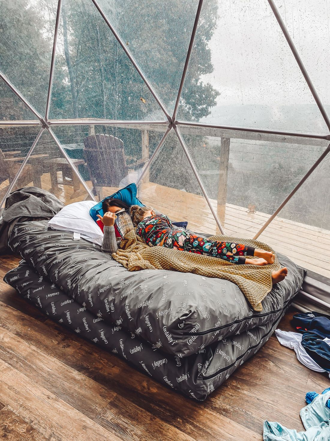 Glamping in Tennessee by popular Nashville lifestyle blog, Modern Day Moguls: image of a mom and her daughter laying together in a bed and reading a book.