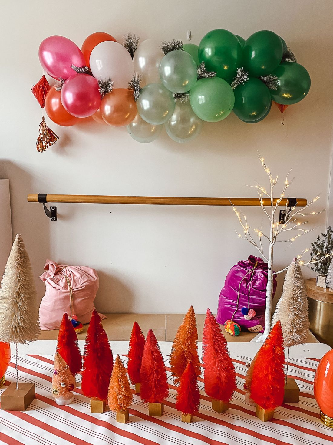DIY Balloon Garland by popular Nashville lifestyle blog, Modern Day Moguls: image of a balloon garland advent calendar hanging on a white wall above two velvet gift sacks and some red, orange and cream colored bottle brush Christmas trees.