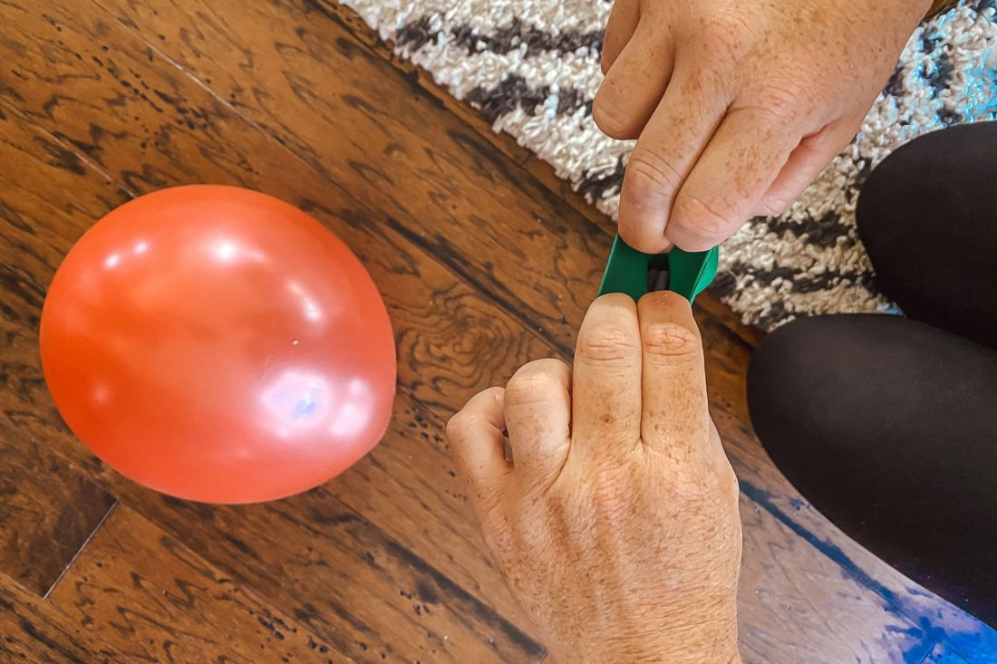 DIY Balloon Garland by popular Nashville lifestyle blog, Modern Day Moguls: image of woman filling balloons with tiny pieces of paper.