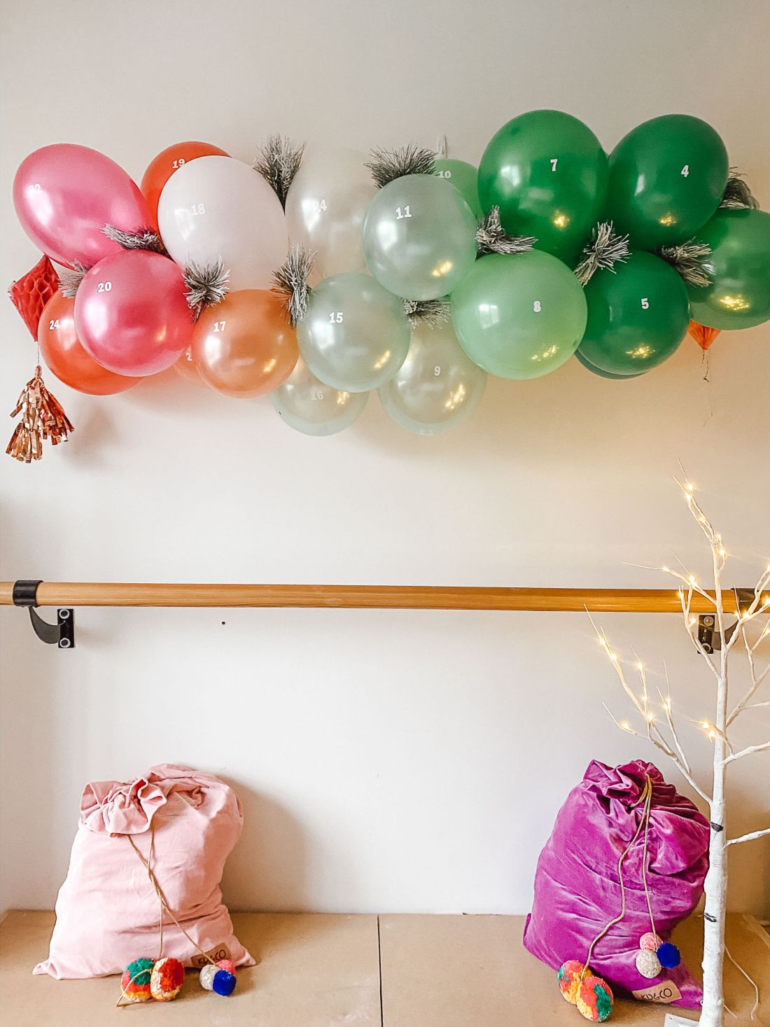 balloon garland advent calendar   DIY Balloon Garland by popular Nashville lifestyle blog, Modern Day Moguls: image of a balloon garland advent calendar hanging on a white wall above two velvet gift sacks.