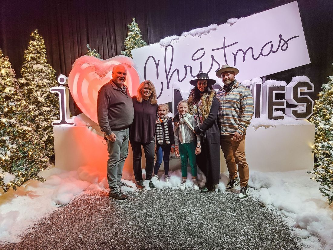 Gaylord Opryland Christmas by popular Nashville blog, Modern Day Moguls: image of a family standing in front of a I Love Christmas Movies display.