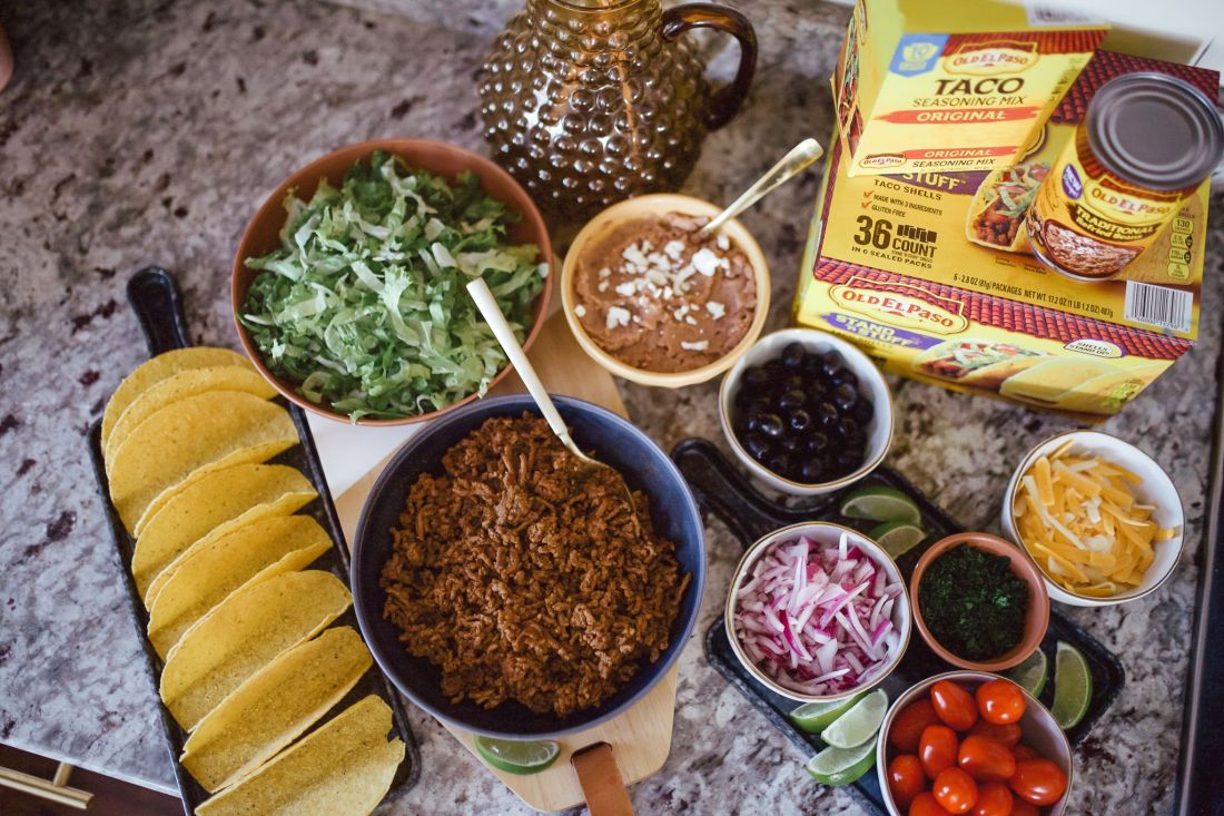 how to do a taco board taco Tuesday | Taco Toppings by popular Nashville lifestyle blog, Modern Day Moguls: image of Old El Paso hard taco shells and bowls of taco meet, shredded lettuce, olives, cherry tomatoes, shredded cheese, refried beans, lime wedges, and diced red onions.