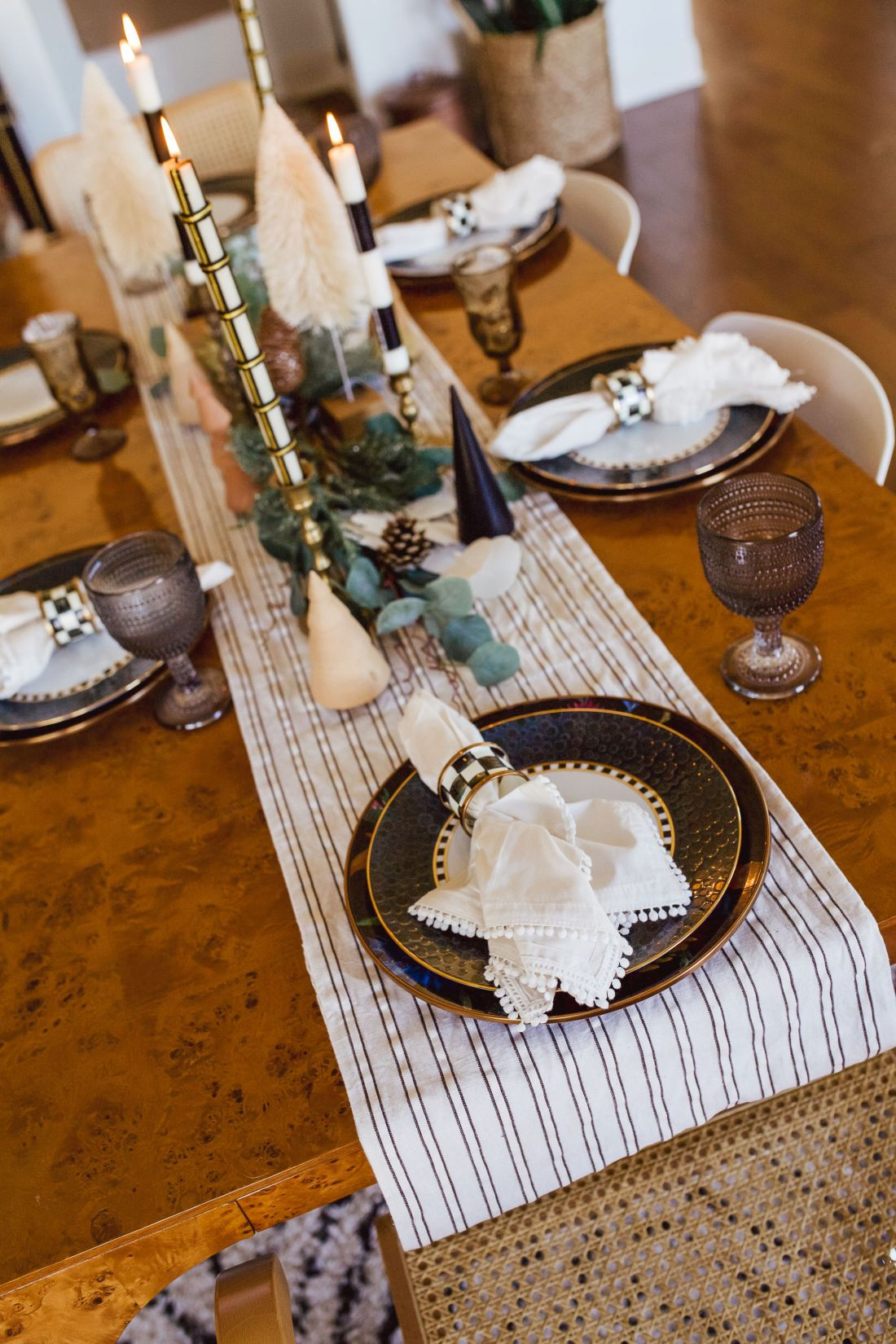 Christmas Tablescape Ideas by popular Nashville life and style blog, Modern Day Moguls: image of a table set with a stripe table runner, blue and gold trim plates, white cloth napkins with Mackenzie-Childs napkin rings, eucalyptus garland, black and white stripe candlesticks, and black hobnail glasses.