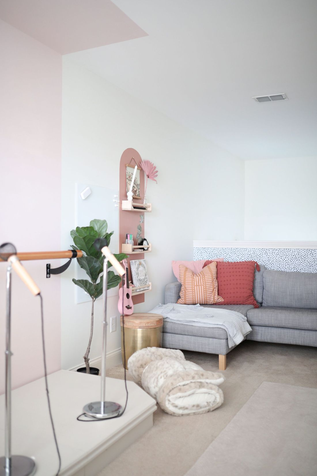 Geometric Shapes Design by popular Nashville life and style blog, Modern Day Moguls: image of a playroom with pink geometric shapes painted on white walls, ballet bar, pink chairs, exercise trampoline, pink ombre tassel light fixture, and a grey sectional couch.