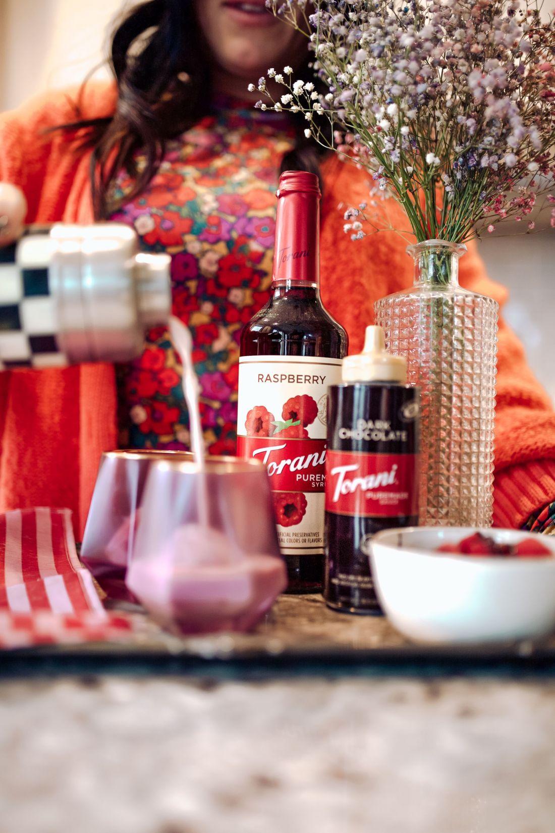 Raspberry Russian by popular Nashville lifestyle blog, Modern Day Moguls: image of purple glasses, raspberries, Torani Dark Chocolate, and Torani raspberry flavoring on a black and white stripe marble cutting board.