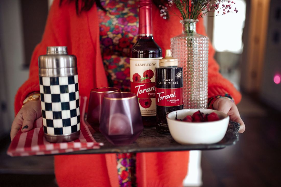 Raspberry Russian by popular Nashville lifestyle blog, Modern Day Moguls: image of a woman carrying a black tray set with, a black and white checked drink shaker, purple glasses, raspberries, Torani Dark Chocolate, and Torani raspberry flavoring.