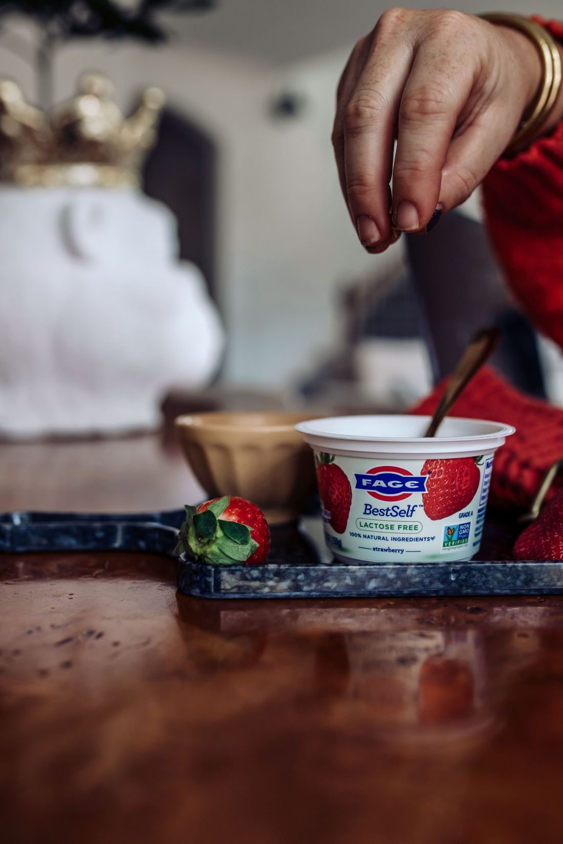 Keeping New Year's Resolutions by popular Nashville lifestyle blog, Modern Day Moguls: image of a woman putting granola in her Fage yogurt cup.