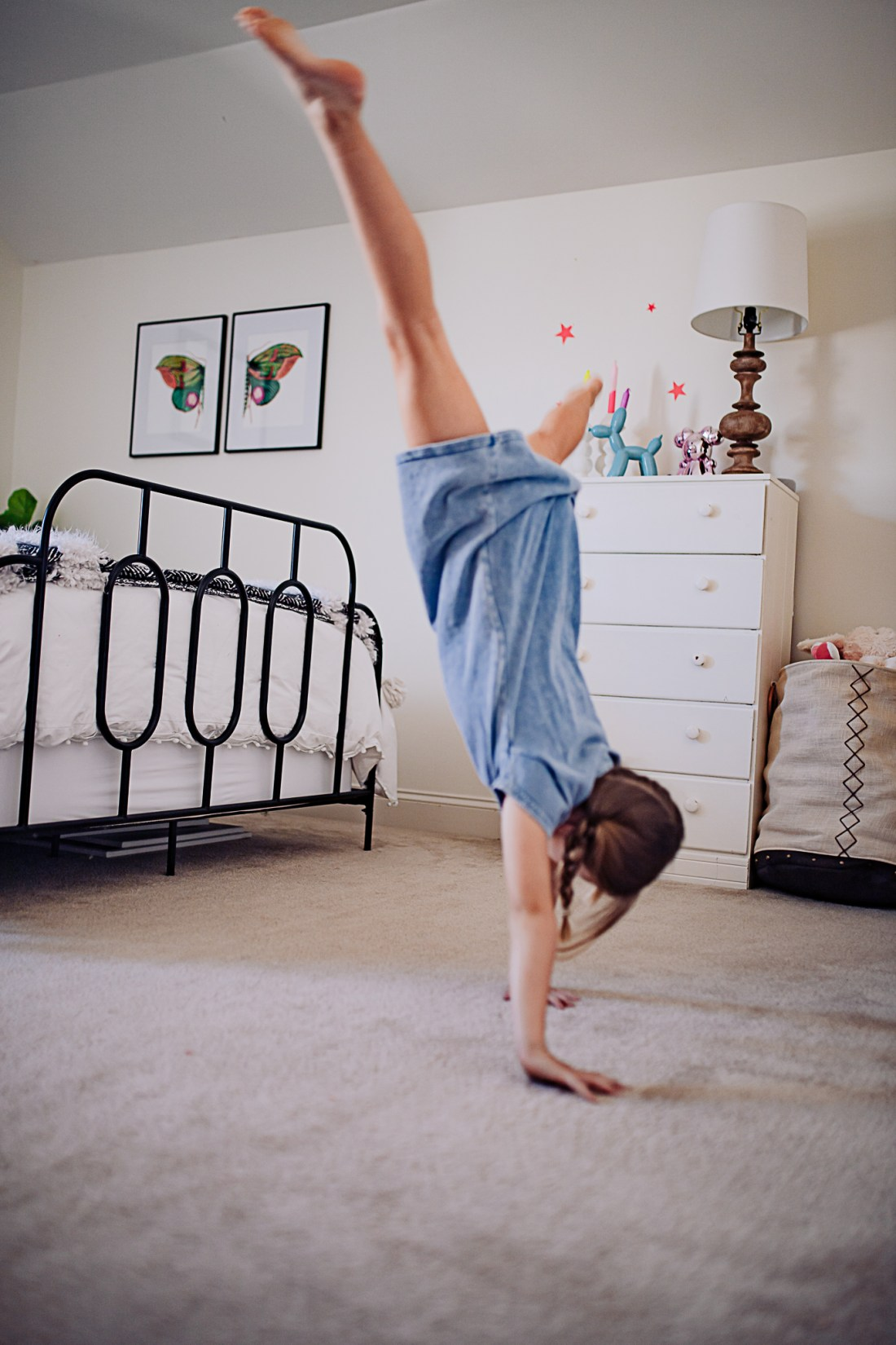 Kids Room by popular Nashville life and style blog, Modern Day Moguls: image of a young girl doing a cartwheel in her room that's decorated with a white dresser, black iron bed frame, and butterfly art prints in black frames.