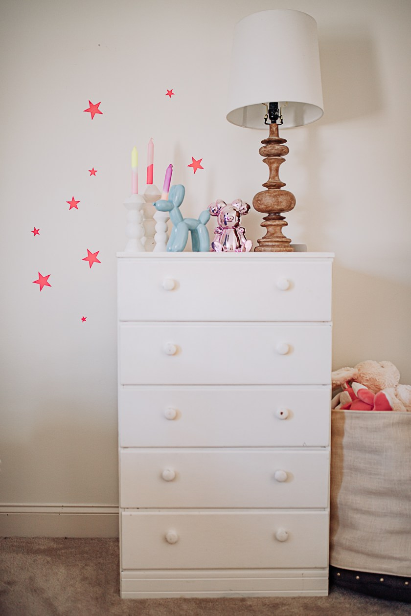 Kids Room by popular Nashville life and style blog, Modern Day Moguls: image of a young girl putting neon pink stars on her wall next to her white dresser decorated with white candlestick holders, wooden lamp with white lamp shade, and glass balloon dog, and pink glass bear decor.