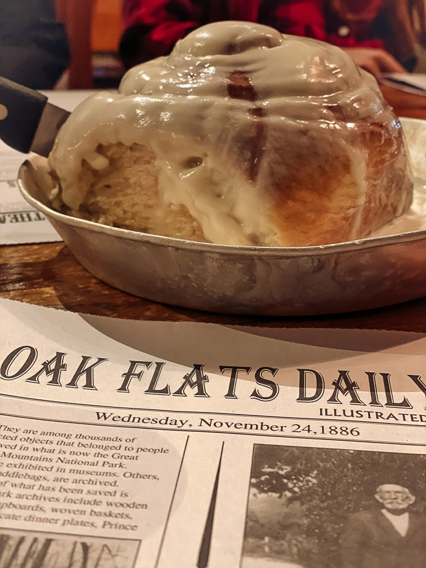Gatlinburg Tennessee by popular Nashville travel blog, Modern Day Moguls: image of Oak Flats Daily newspaper and a large cinnamon roll in a tin dish.
