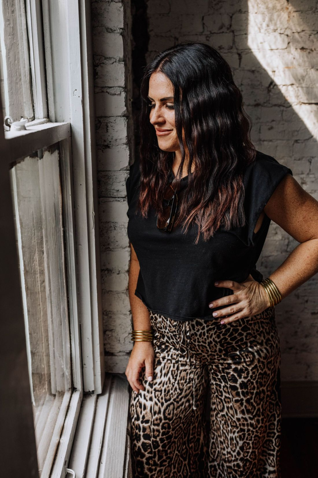 Hair Cut by popular Nashville beauty blog, Modern Day Moguls: image of a woman standing next oat window and wearing a black shirt, gold bracelets, and wide leg leopard print pants.