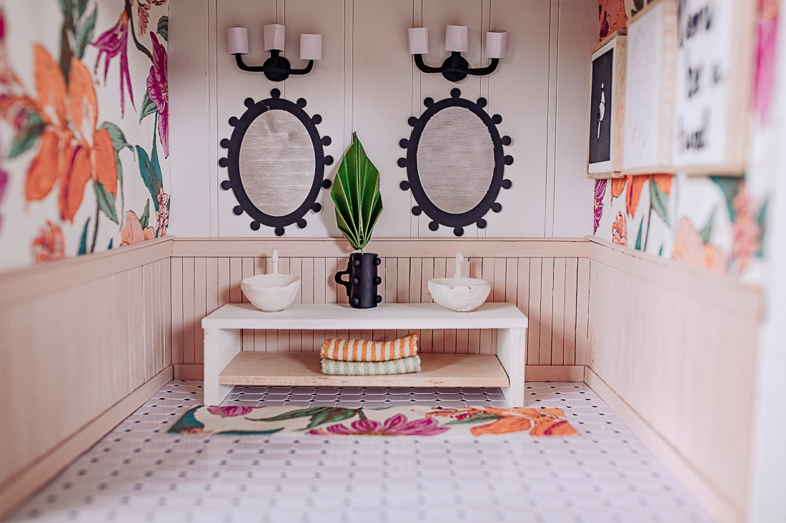 Dollhouse Accessories by popular Nashville life and style blog, Modern Day Moguls: image of a dollhouse bathroom with floral wallpaper, white tile flooring, black oval frame mirrors, floral rug, and white vanity with white sinks.