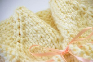 close up of a baby sweater made from off-white yarn and a pink ribbon