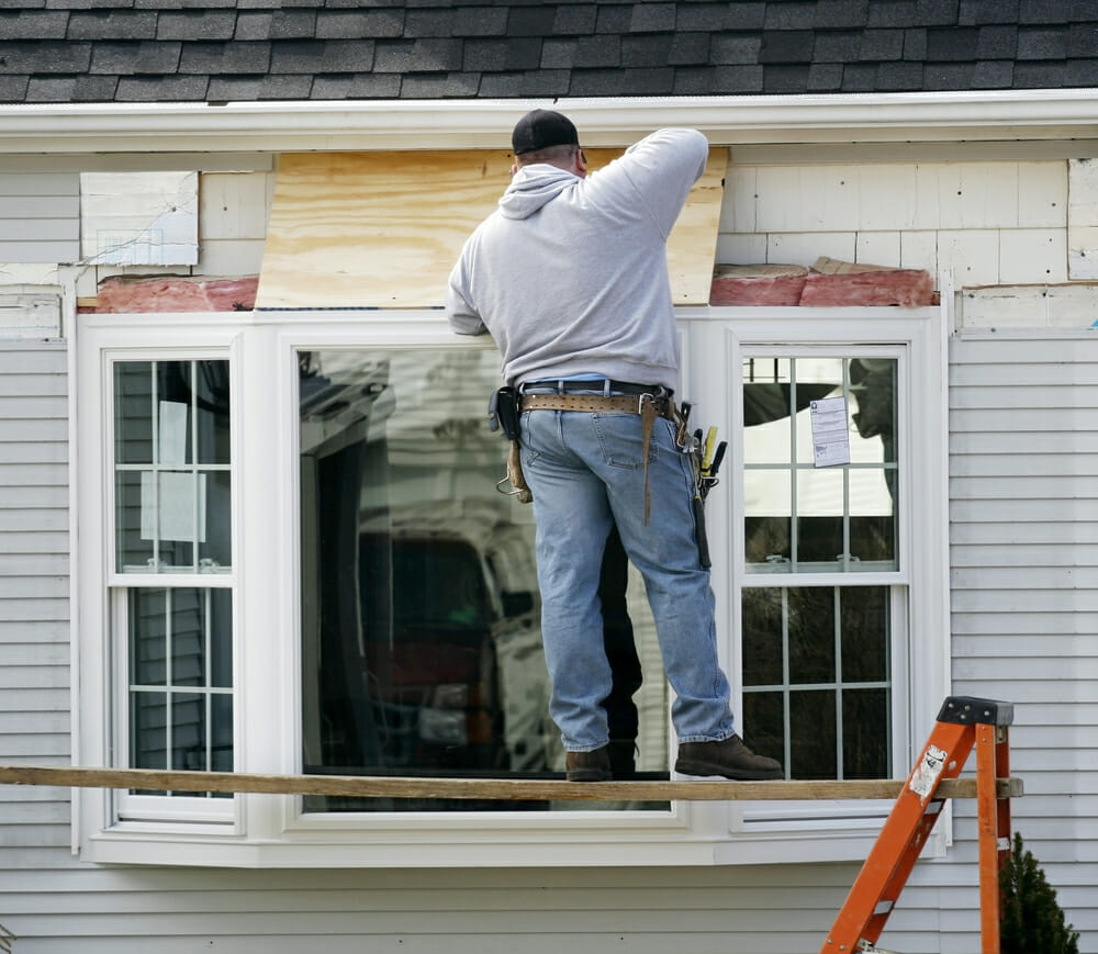 hight resolution of a contractor installs a bay window into a home