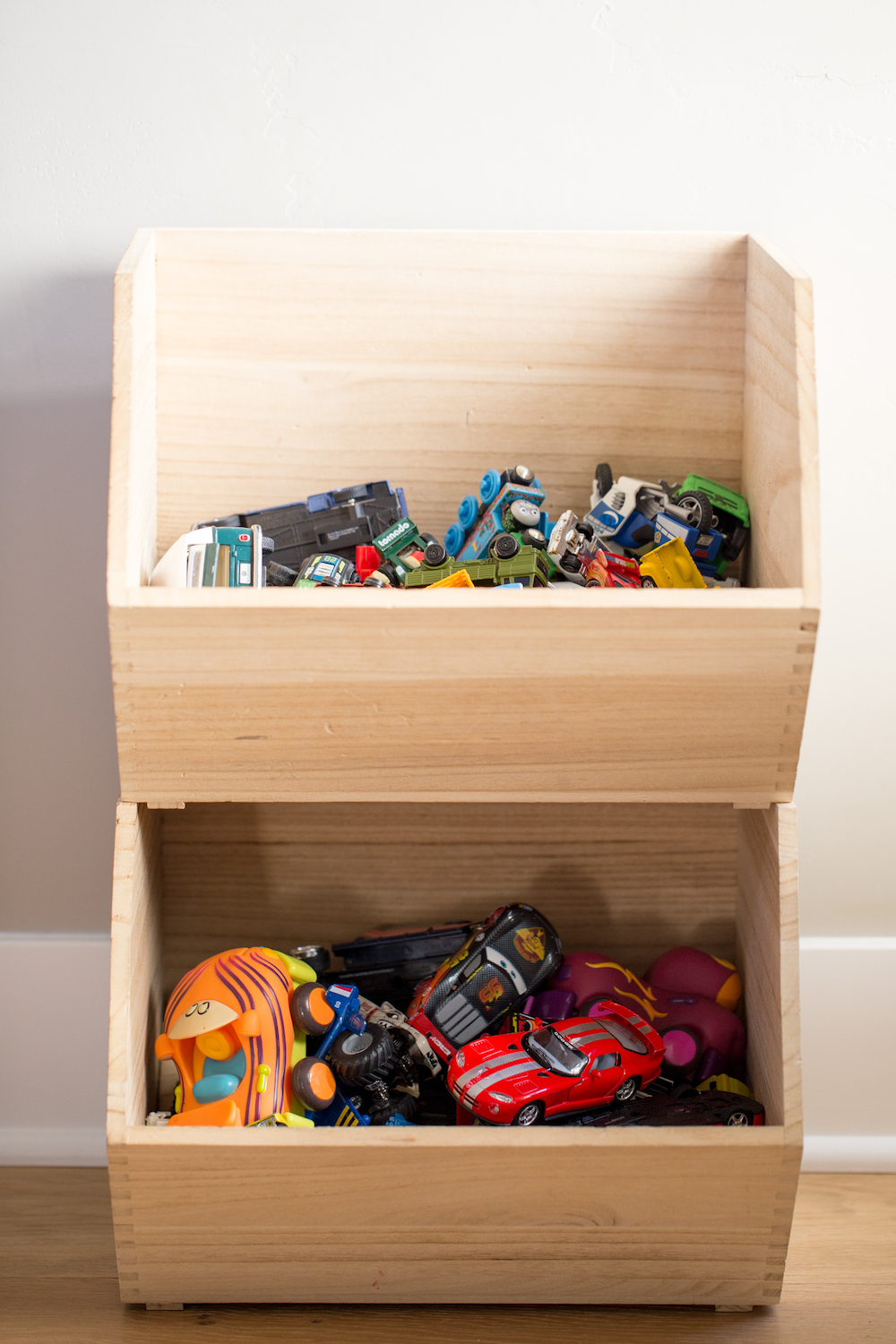 stacked wooden toy storage boxes with toy cars inside