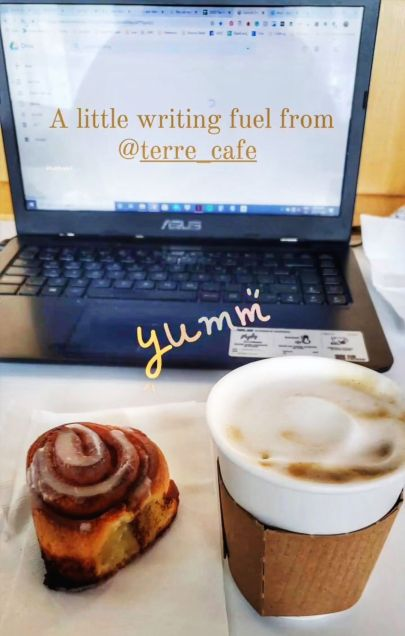A cinnamon bun and cappuccino from Terre Cafe sitting in front of a laptop on a desk at Alt Hotel