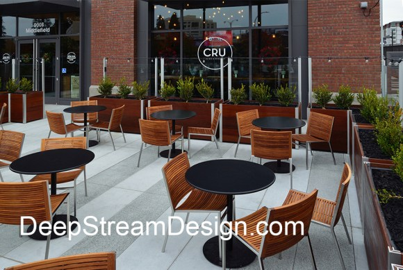 planters with glass windscreen create an upscale sidewalk restaurant