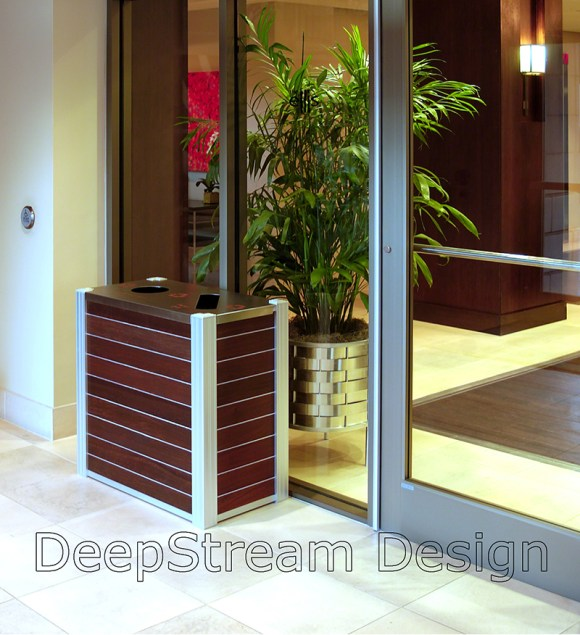 Top loading Audubon Modern Wood Combination Recycling and Trash Receptacle in a hotel lobby