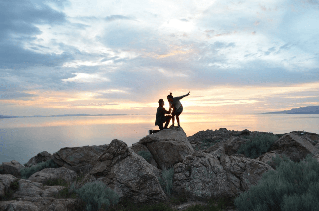 Man proposing to woman on rocks on beach at sunset