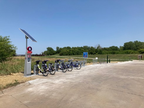 Near the edge of a trail, with blue sky and green trees in the background, a new bike share station with 5 bikes is next to a bike rack for parking and a green fixit station with tools and pump.
