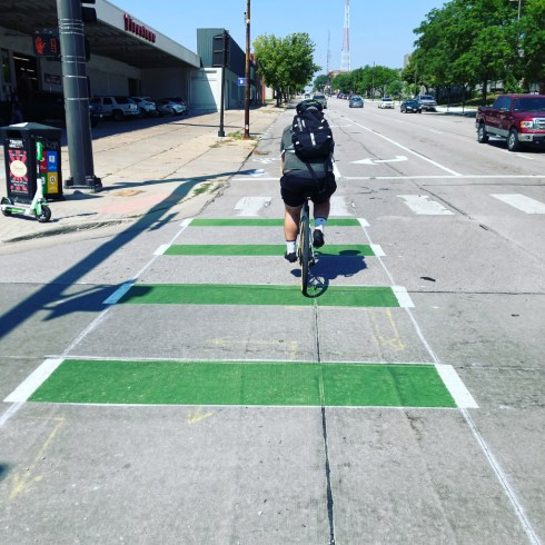 A person on a bike wearing a backpack is pedaling west on Harney Street through an intersection with green paint striping.