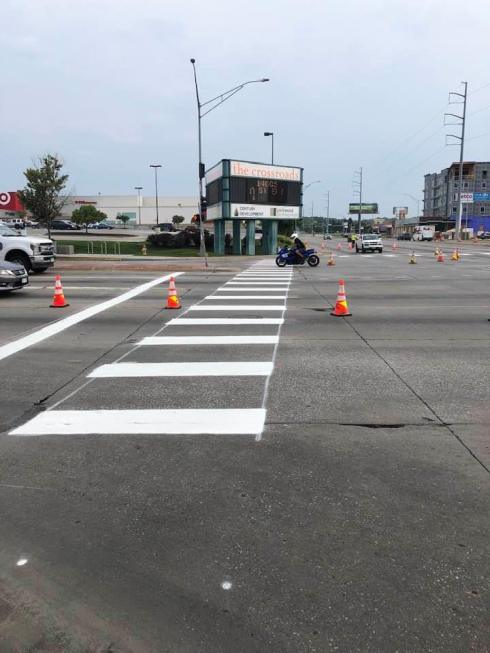 Photo of fresh white painted crosswalk stripes and stop bar at the corner of 72nd & Dodge looking north toward the Crossroads corner. There are orange construction cones alerting drivers to the new paint.