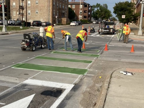 A construction crew working on the Harney Street cycle track. This is an intersection being painted green. There are orange traffic cones blocking off the area with white bike images in the bike lanes.