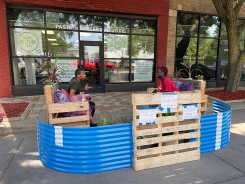 A parklet on N. 24th St. built with pallets and blue rounded corrugated aluminum. Two people are seated on the pallet benches, chatting in what was a parking spot for a car, turned into a gathering spot for the neighborhood.