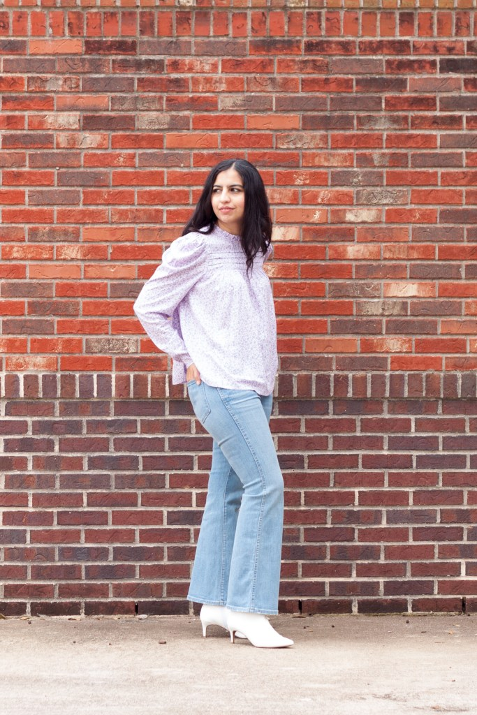 modest flare jeans outfit idea puff sleeve top and light blue flare jeans and white boots