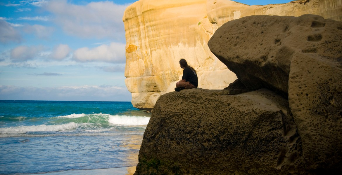 A man sits on a large boulder at Dunedin, New Zealand's Tunnel Beach. The sun illuminates a large cliff in the distance as blue and green waves crash on the shore.