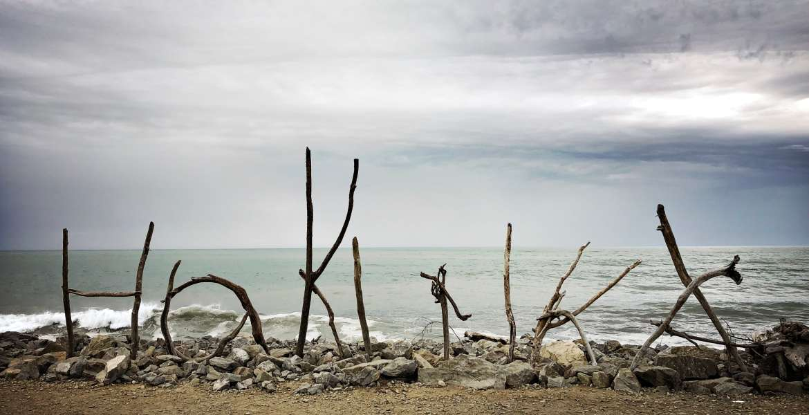 "A stylized sign made of driftwood spells ""Hokitika"" on the West Coast shore of New Zealand, looking out to the Tasman Sea."
