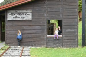 A mother and daughter pose in an open window at the Brunner, New Zealand, while another daughter stands nearby, on railroad tracks that lead toward a museum building on the site.