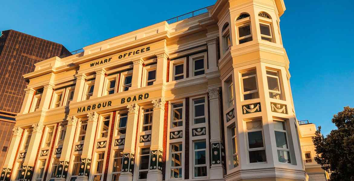 The historic Wharf Offices and Harbour Board on Wellington, New Zealand's waterfront at Lambton Harbour. Early morning golden light illuminates the building.