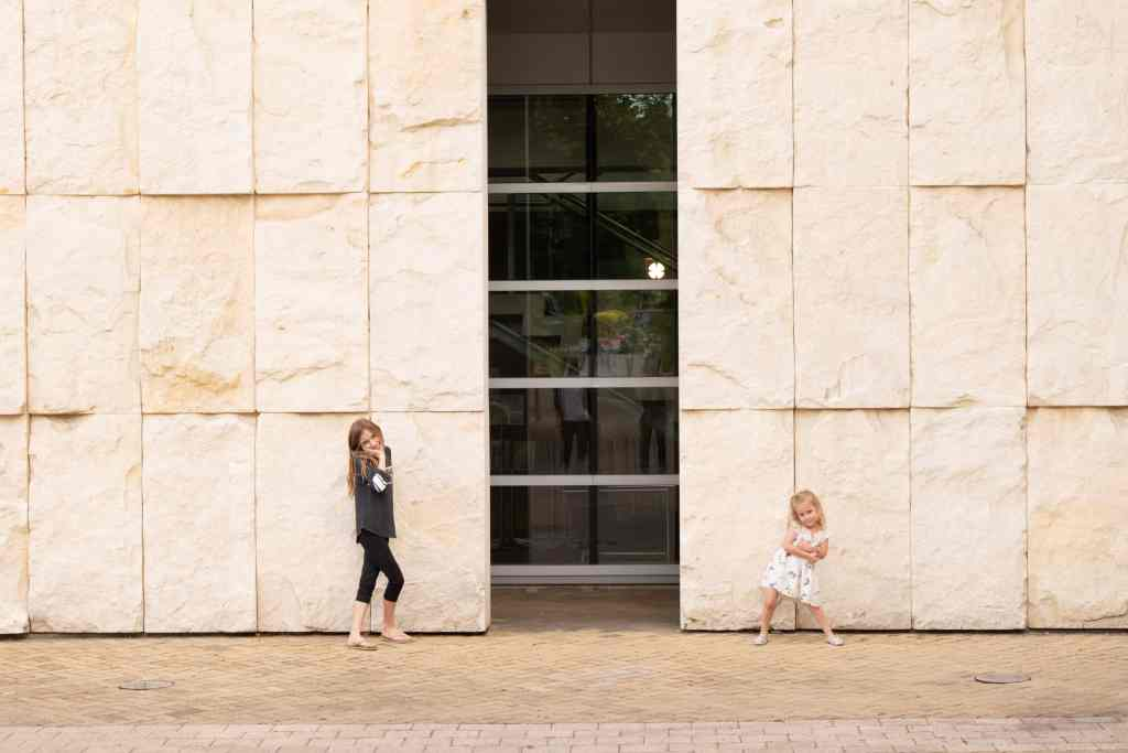Two young sisters pose near a wall of Oamaru white stone outside the University of Otago's library in Dunedin, New Zealand.
