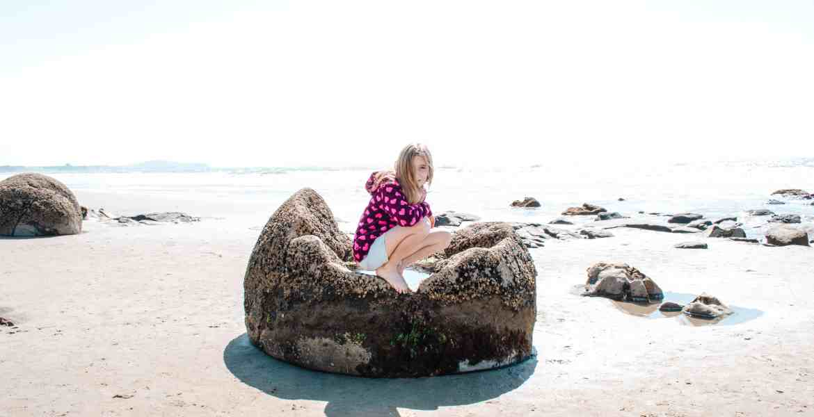 A young girl crouches inside a massive Moeraki Boulder sitting on the sandy Pacific Coast of New Zealand. The top of the boulder has eroded, leaving a large, concave opening in which the girl sits. The Pacific Ocean is visible off New Zealand's South Island on the East Coast near the village of Moeraki.